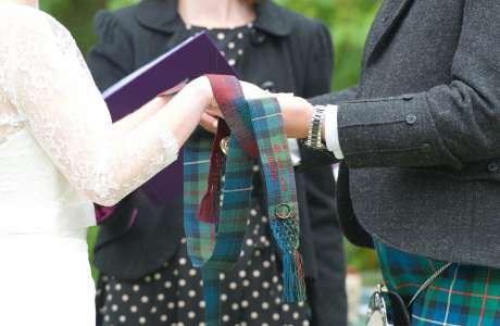 Tartan from each family, detail embroidered on each ribbon and with a ring and locket from the absent grandparents embroidered on with silk twist